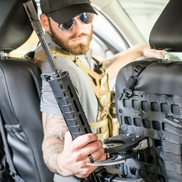 guy unlocking ar15 from molle panel in truck